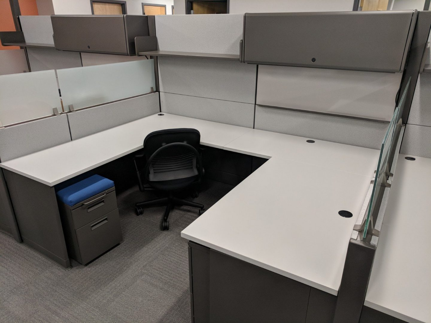 cubicle with an office chair and file cabinet