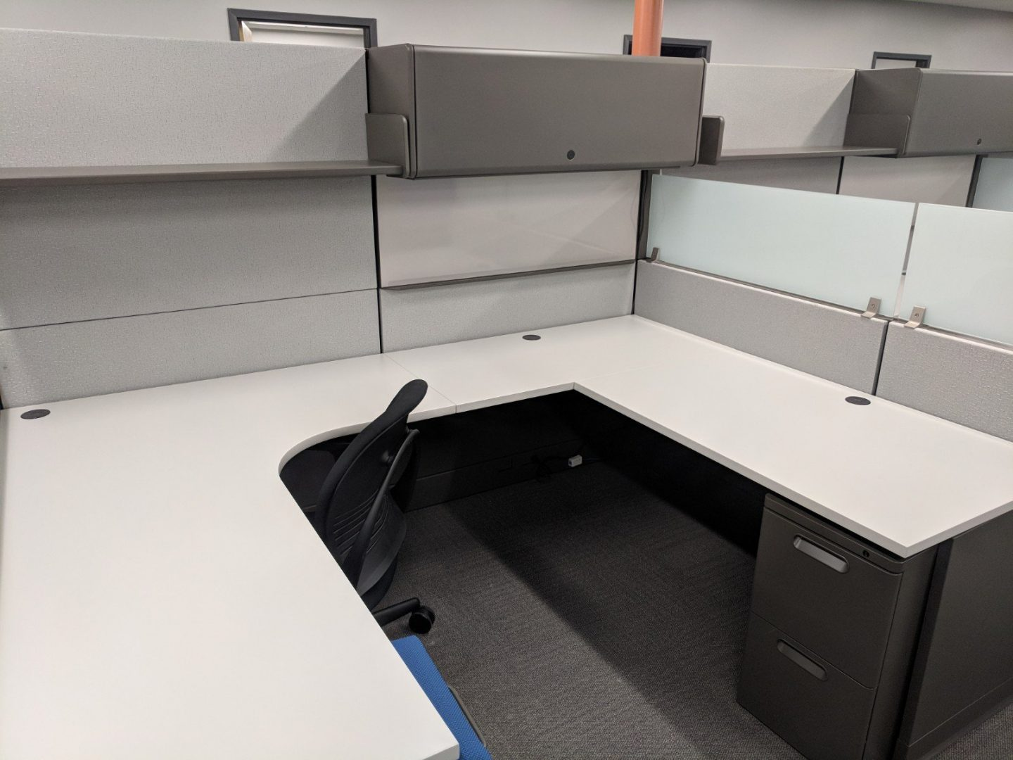 cubicle with u-shaped desk and file cabinet
